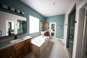 Bathroom with walk-in shower, tub, and two sinks - Houston plumbing remodels